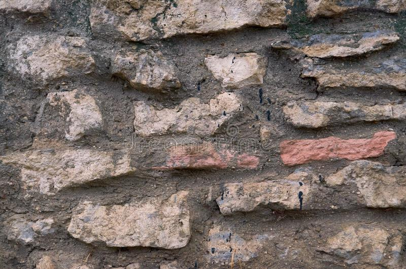 Old stone wall outdoors for background, texture. Natural stone masonry royalty free stock photo