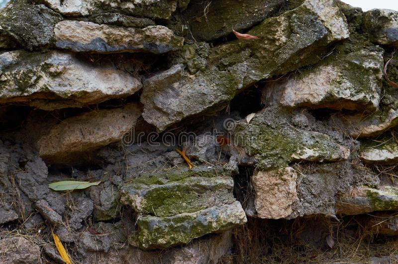 Old stone wall outdoors for background, texture. Natural stone masonry stock image