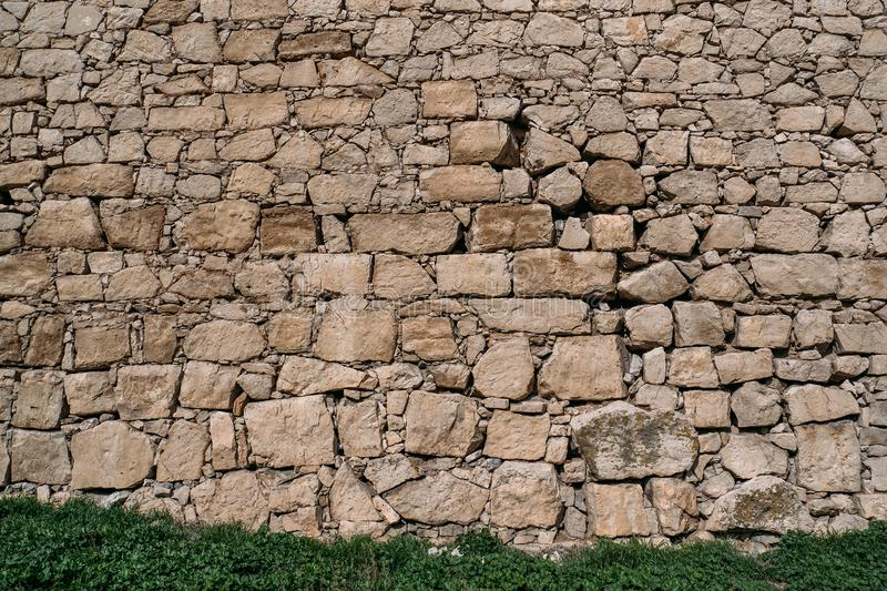 Old stone wall texture with green grass, blocks of ancient castle surface as background for design stock photos