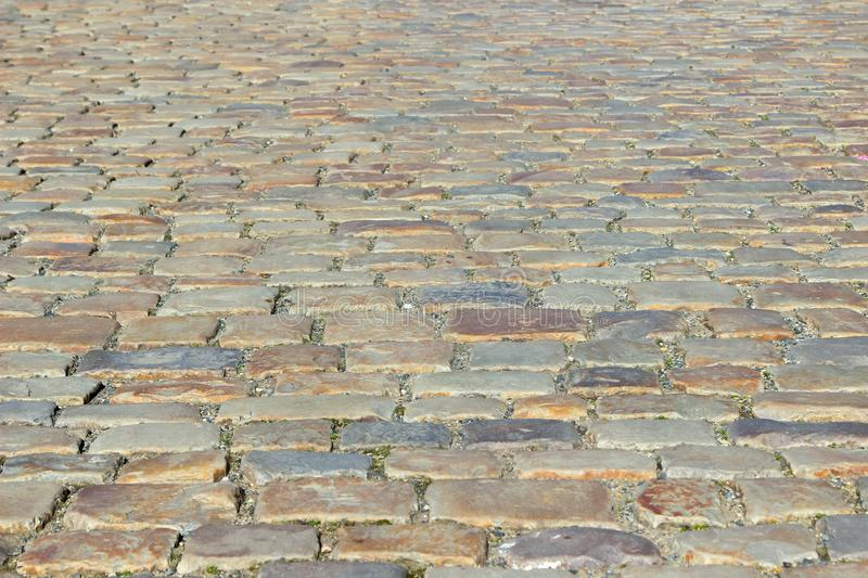 An old stoneblock pavement cobbled with natural stone blocks of different colors. Photo in perspective with selective focus royalty free stock photography