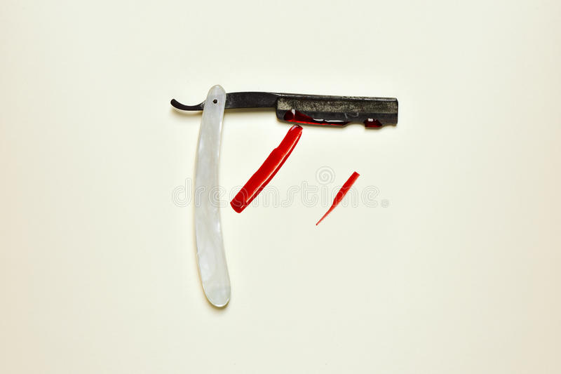 Old straight razor full of blood. An old and rusty straight razor full of blood on an off-white background stock photography