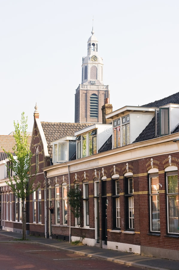 Old street. Old Dutch houses with churchtower in the background royalty free stock photos
