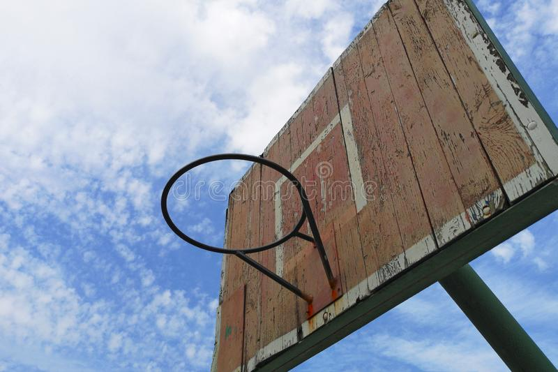 Old street basketball ring against the sky. Old wooden basketball shield against the blue sky. Copy space stock photography