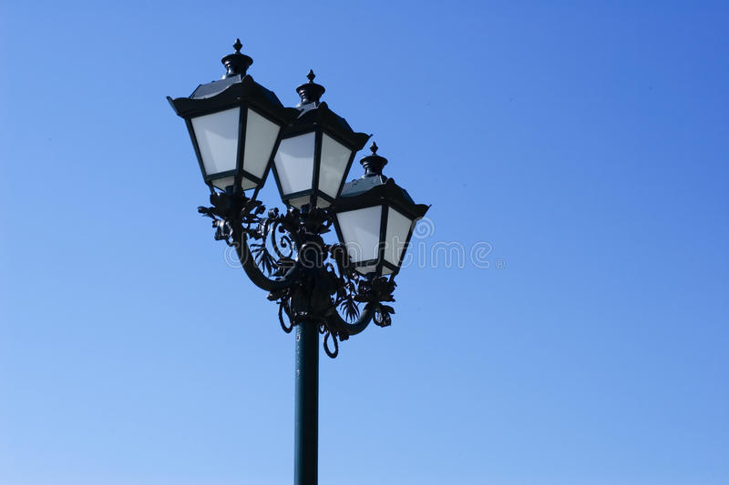Old street lamp. On a blue sky background royalty free stock photo