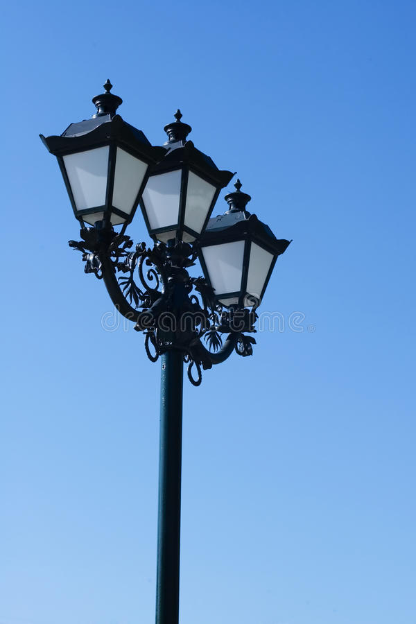 Old street lamp background. Vintage street lamp on a blue sky background stock images