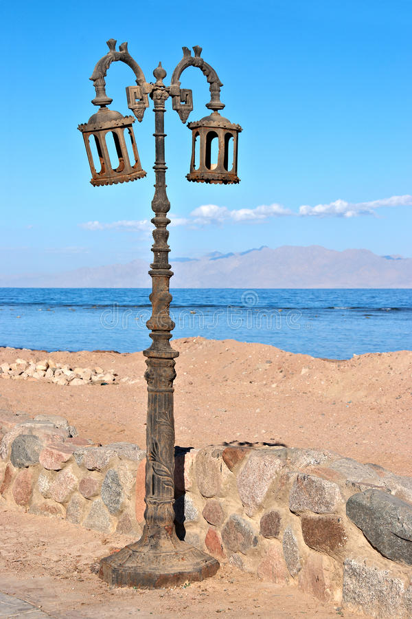 Old street lamp on the beach royalty free stock image
