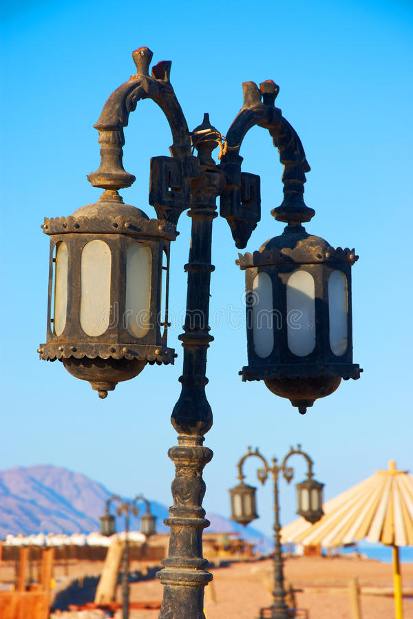 Old street lamp on the beach royalty free stock photo