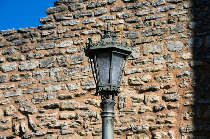 Old Street lamp with a stone brick wall in the background. Ronda, Spain stock image