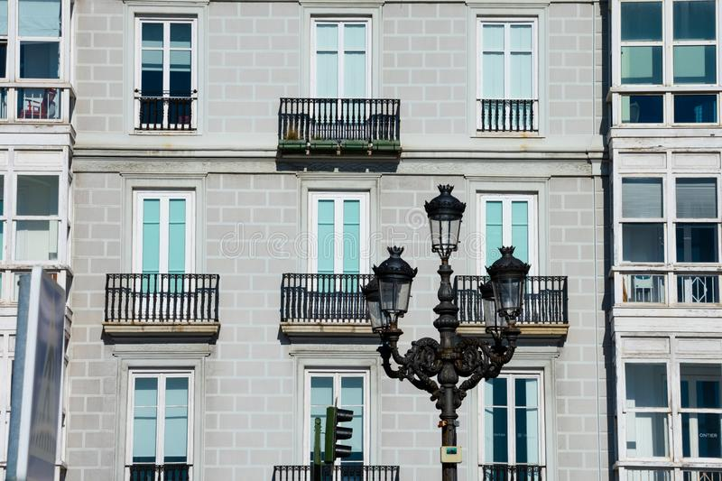 Old street lamp with typical spanish houses in the background. Santander, Spain royalty free stock images