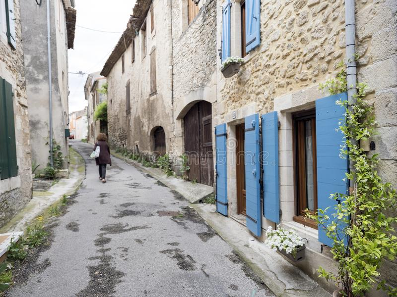 Old street with lonely figure and house with shutters and plants in manosque stock images