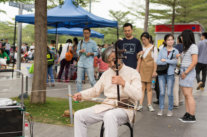 An old street musician. Playing Erhu, a two-stringed bowed instrument in China (Chinese Violin royalty free stock photos