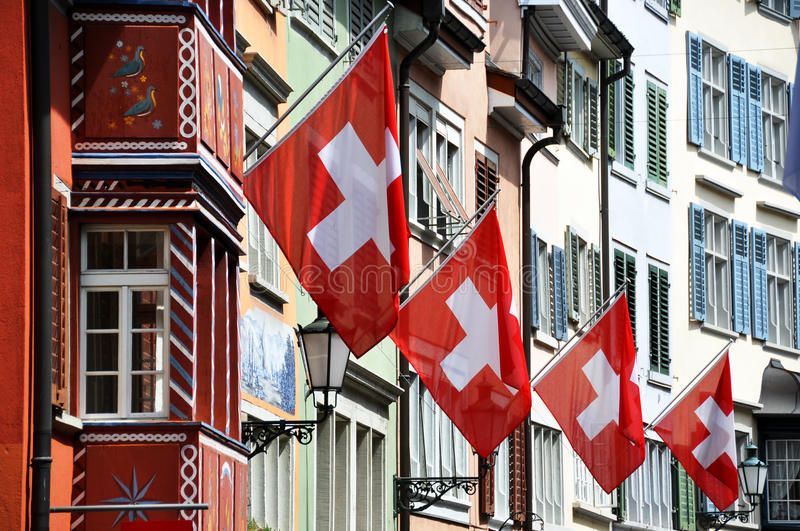 Old street in Zurich decorated with flags royalty free stock photo