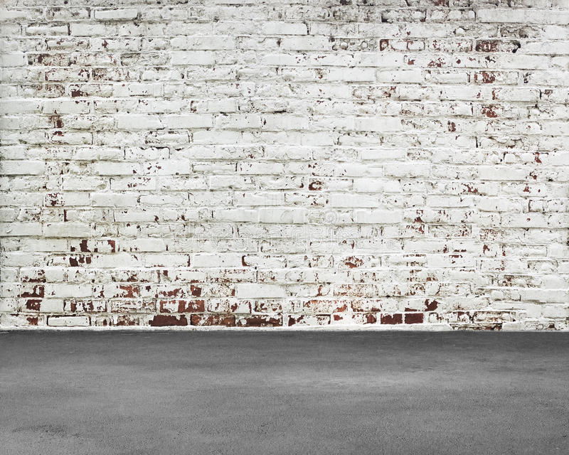 Old stripped bricks wall with dirty concrete floor. Nobody stock image