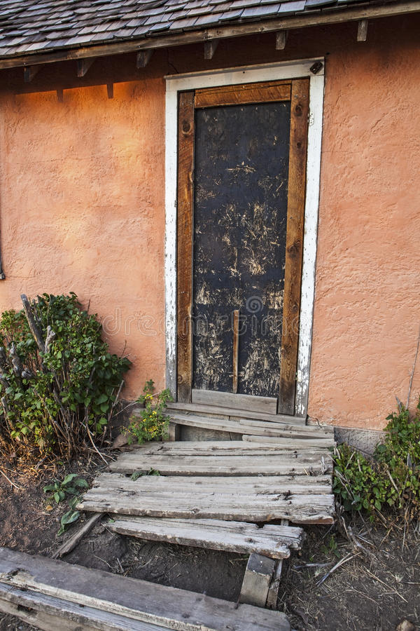 Old stucco cement house and dilapidated porch royalty free stock image