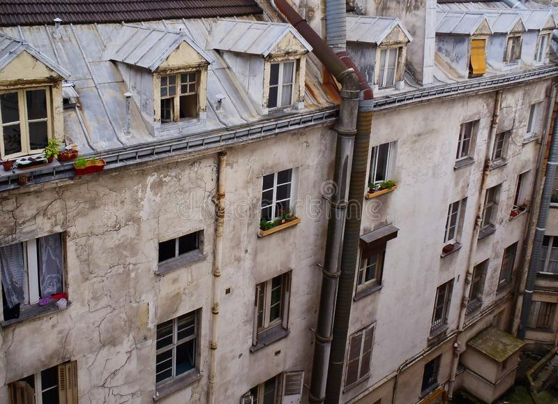 Old Style Apartment Building With Dormer Windows, Paris, France. An old style pale stucco apartment building, with dormer Garrett windows on top level, Paris stock photo