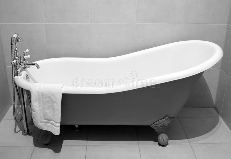Old style bath tub with metal legs. And towel, vintage style on b&w tone