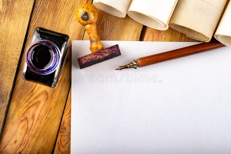 Old style calligraphy nib, ink and blank card on a wooden table. Writing accessories prepared for work. Dark background, bottle, above, brown, copy, copyspace stock photos