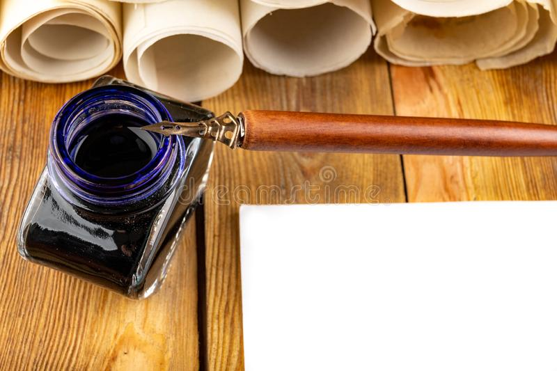 Old style calligraphy nib, ink and blank card on a wooden table. Writing accessories prepared for work. Dark background, bottle, above, brown, copy, copyspace stock images