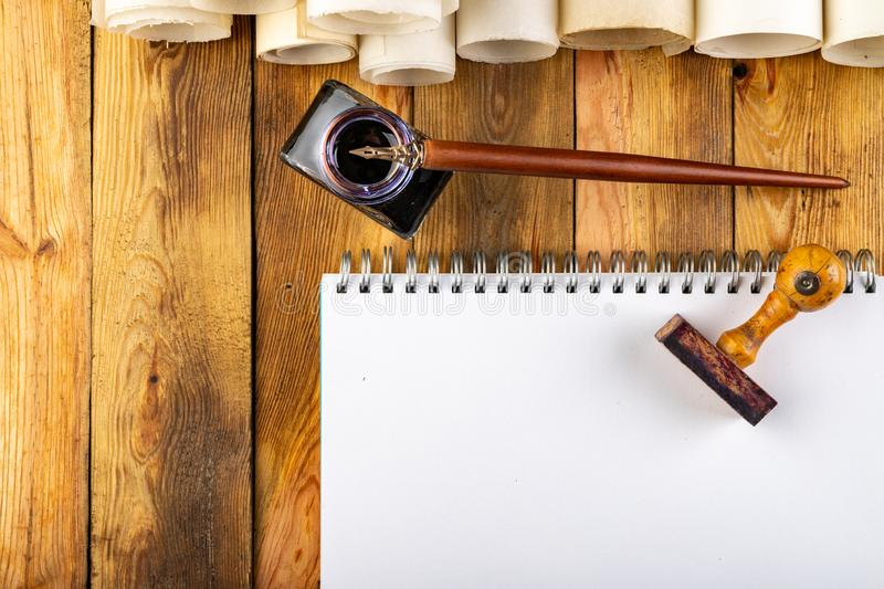 Old style calligraphy nib, ink and blank card on a wooden table. Writing accessories prepared for work. Dark background, bottle, above, brown, copy, copyspace royalty free stock photography