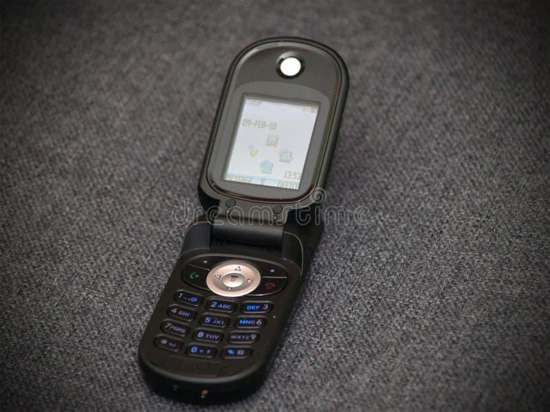 Old style classic black flip cellular phone stock photo