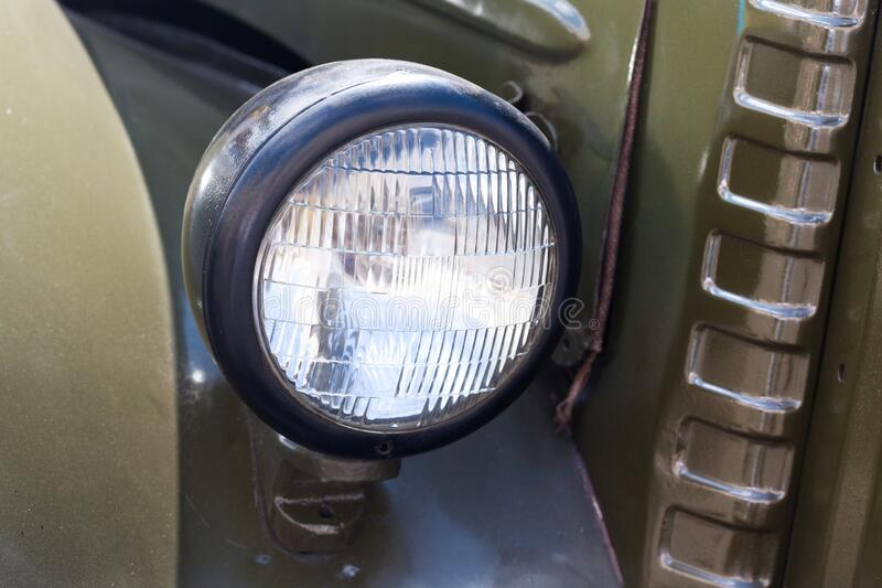 Old style dark green truck lamp. Vintage automobile front side. Closeup. soft focus. royalty free stock photo