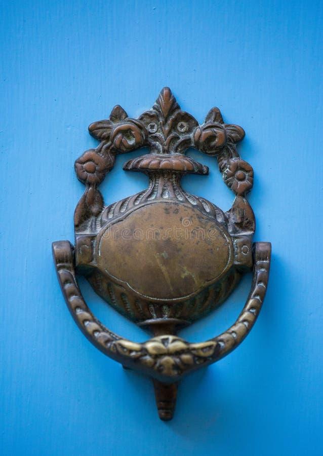 An old style decorative bronze door handle on a wooden azure door, the distinctive feature and symbol of Malta in Mdina. An old style decorative bronze door stock photos