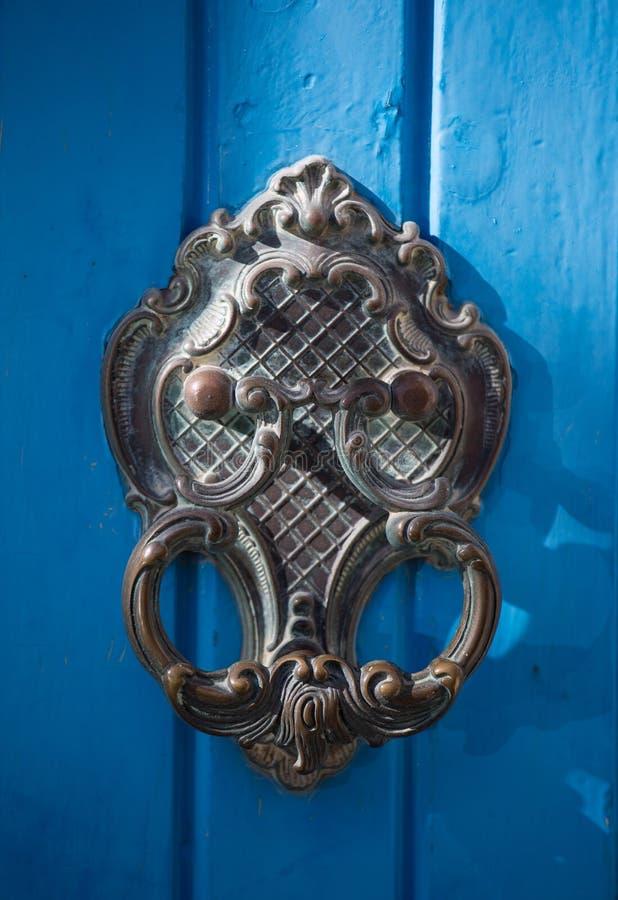 An old style decorative bronze door handle on a wooden azure door, the distinctive feature and symbol of Malta in Mdina. An old style decorative bronze door stock images