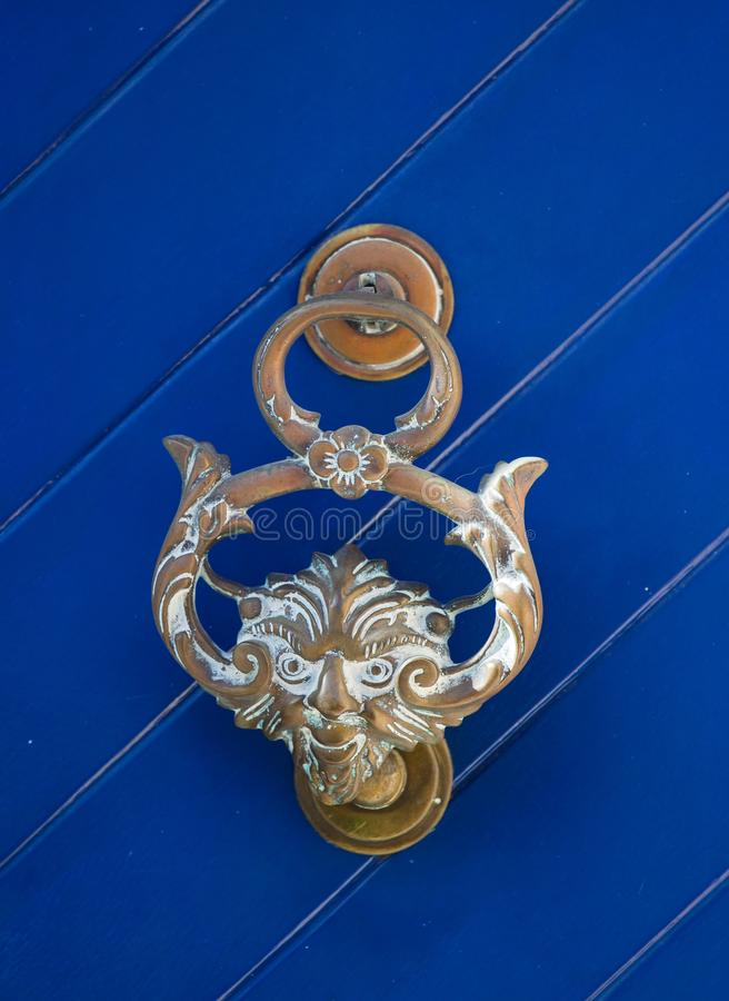 An old style decorative bronze door handle on a wooden azure door, the distinctive feature and symbol of Malta in Mdina. An old style decorative bronze door stock photography