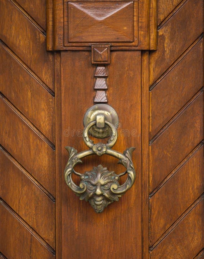 An old style decorative bronze door handle on a wooden door, the distinctive feature and symbol of Malta in Mdina. An old style decorative bronze door handle on royalty free stock photo