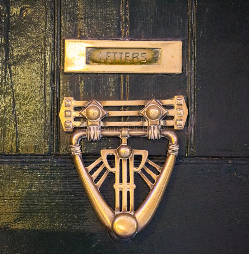 An old style decorative bronze door handle on a wooden door, the distinctive feature and symbol of Malta in Mdina. An old style decorative bronze door handle on stock images