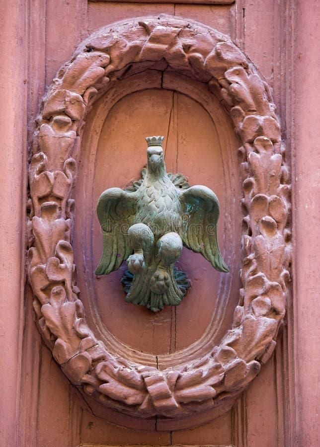 An old style decorative bronze door handle on a wooden door, the distinctive feature and symbol of Malta in Mdina. An old style decorative bronze door handle on stock image