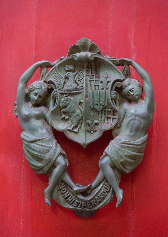 An old style decorative bronze door handle on a wooden red door, the distinctive feature and symbol of Malta in Mdina. An old style decorative bronze door royalty free stock images