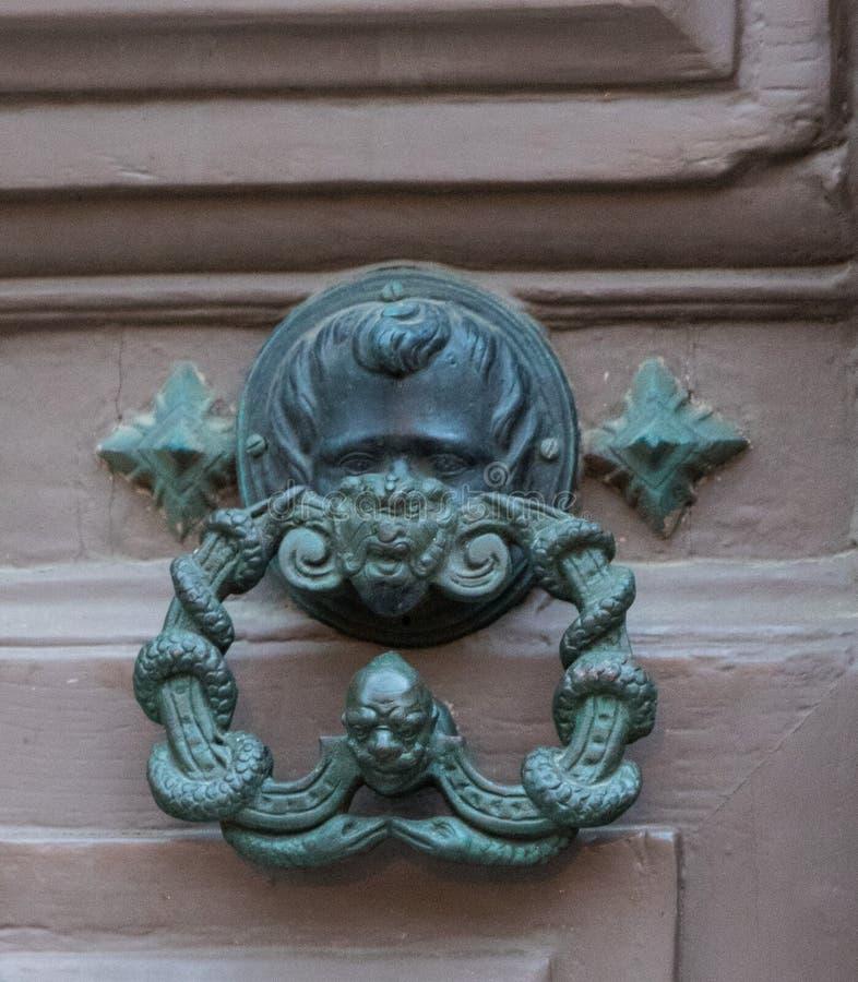 An old style decorative bronze door handle on a wooden door, the distinctive feature and symbol of Malta in Mdina. An old style decorative bronze door handle on stock photo
