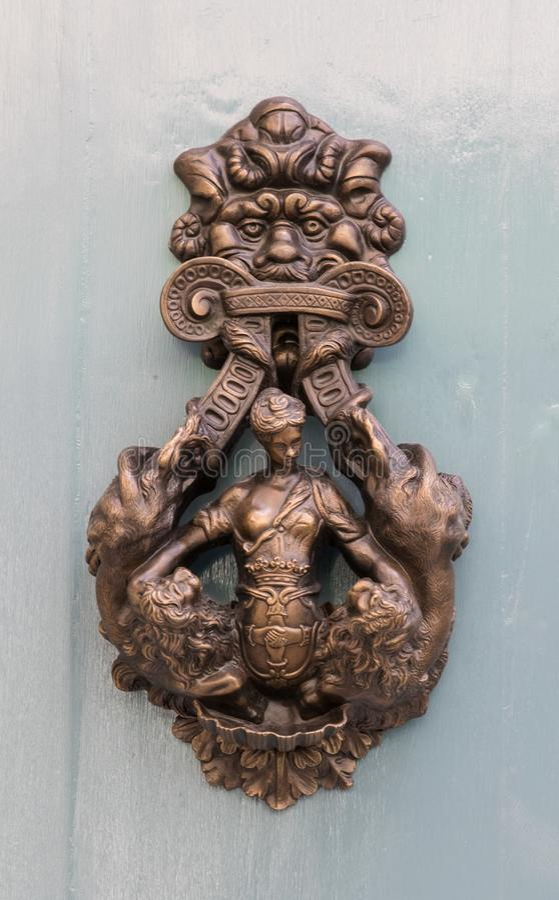 An old style decorative bronze door handle on a wooden door, the distinctive feature and symbol of Malta in Mdina. An old style decorative bronze door handle on stock photography
