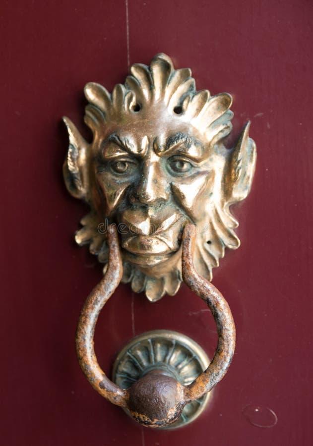 An old style decorative bronze door handle on a wooden door, the distinctive feature and symbol of Malta in Mdina. An old style decorative bronze door handle on royalty free stock image
