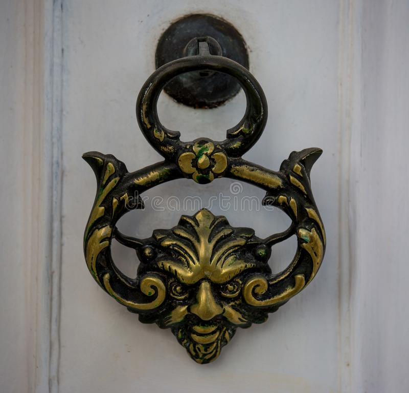 An old style decorative bronze door handle on a wooden door, the distinctive feature and symbol of Malta in Mdina. An old style decorative bronze door handle on royalty free stock photography