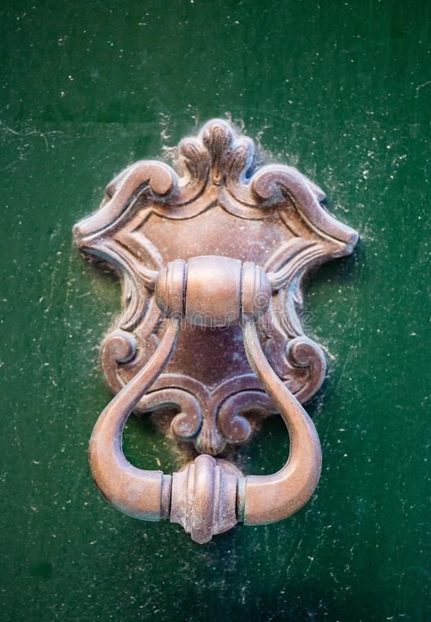 An old style decorative bronze door handle on a wooden green door, the distinctive feature and symbol of Malta in Mdina. An old style decorative bronze door stock images