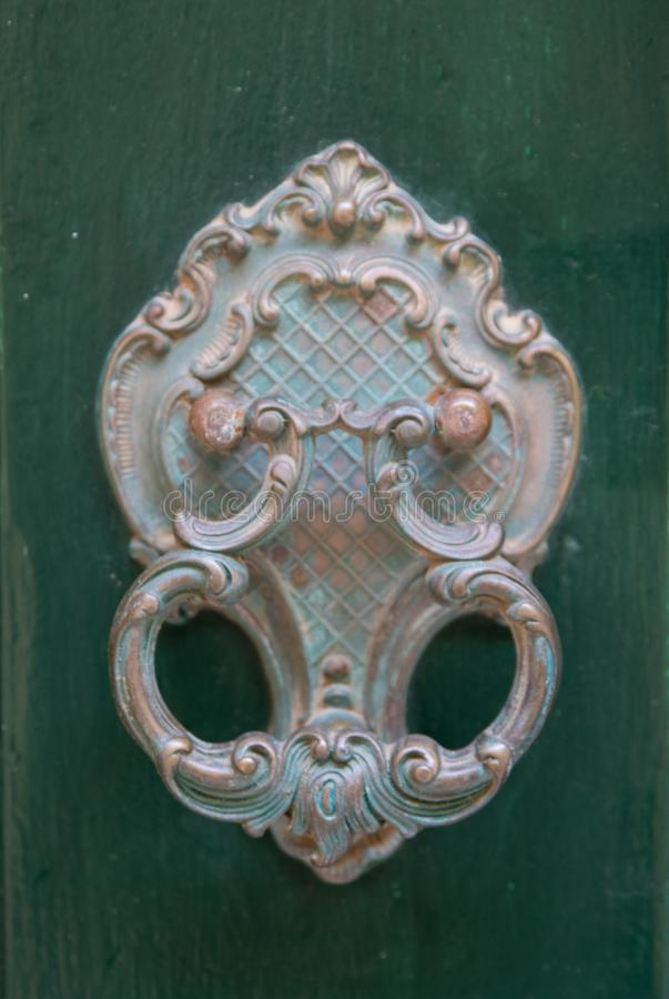 An old style decorative bronze door handle on a wooden green door, the distinctive feature and symbol of Malta in Mdina. An old style decorative bronze door stock photo