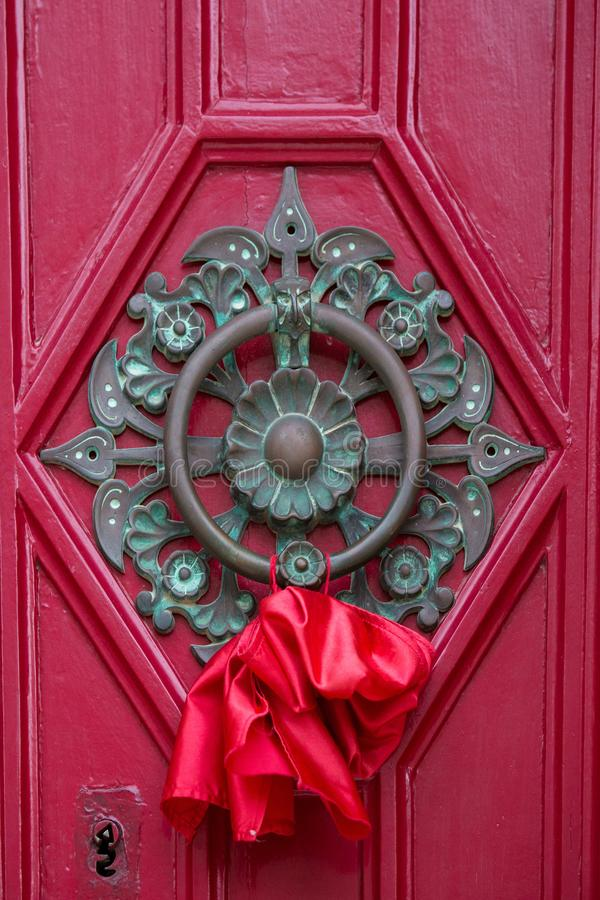 An old style decorative bronze door handle on a wooden red door, the distinctive feature and symbol of Malta in Mdina. An old style decorative bronze door stock image