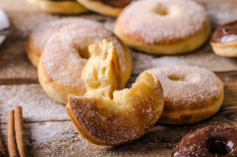 Old style donuts rustic style. Old style donuts with sugar and dark chocolate, whole table, place for your advertising royalty free stock photography