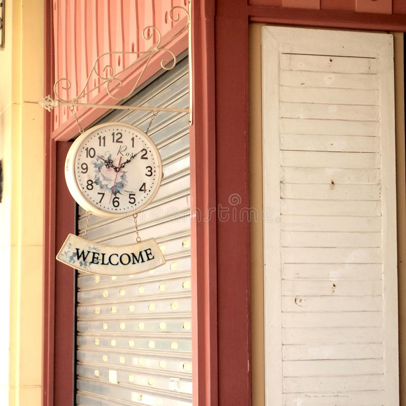 Old style hanging clock with welcome sign on wall. Close up stock photos