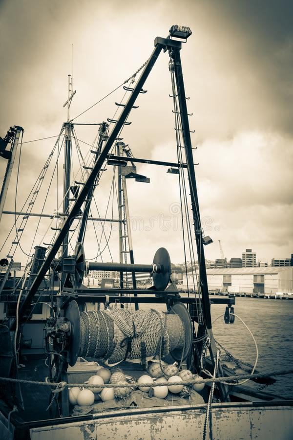 Old style image commercial fishing boats gear and nets moored at Wharf Wellington stock photos