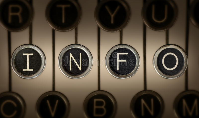 Old Style Information. Close up of old manual typewriter keyboard with scratched chrome keys that spell out INFO. Lighting and focus are centered on INFO keys royalty free stock photos