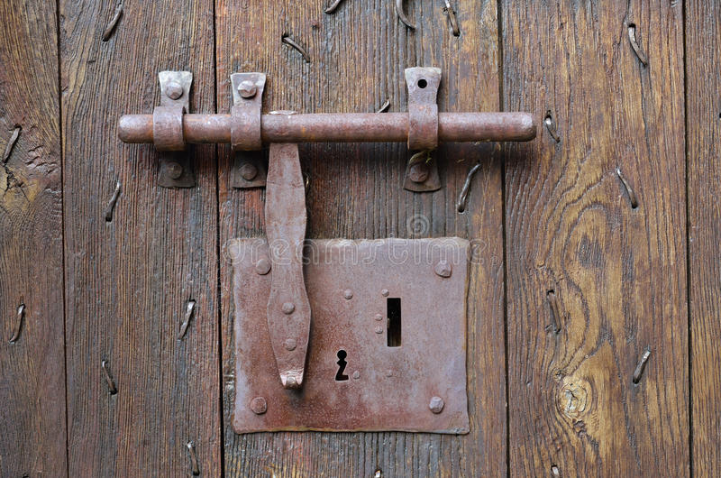 Old-style lock with a hasp on the timber entrance. The big metal lock with a latch on the wooden surface of the ancient batten door royalty free stock photo
