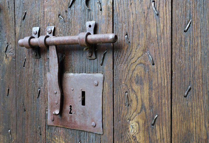 Old-style lock with a hasp on the timber entrance. The big metal lock with a latch on the wooden surface of the ancient batten door stock image