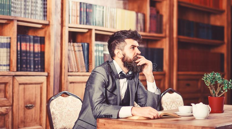 Old style and male fashion. Bearded man sits in library with old book. Mature man in smart suit thinks. Professor with royalty free stock photos