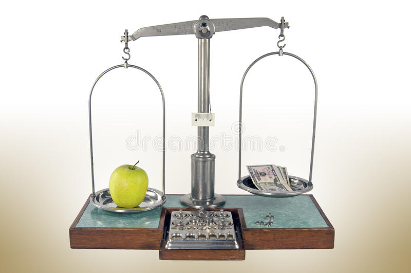 Old style pharmacy scale with apple and money. Traditional old style pharmacy scale with yellow apple and money, small weights royalty free stock photo