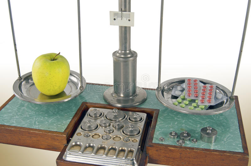 Old style pharmacy scale balanced by apple and drugs. Traditional old style pharmacy scale balanced by yellow apple and drugs, small weights stock photo
