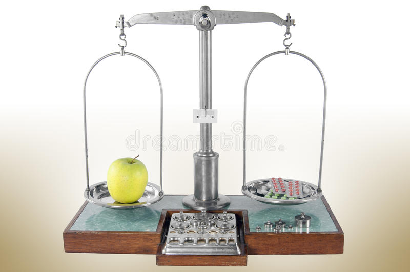 Old style pharmacy scale balanced by apple and drugs. Traditional old style pharmacy scale balanced by yellow apple and drugs, small weights stock photos