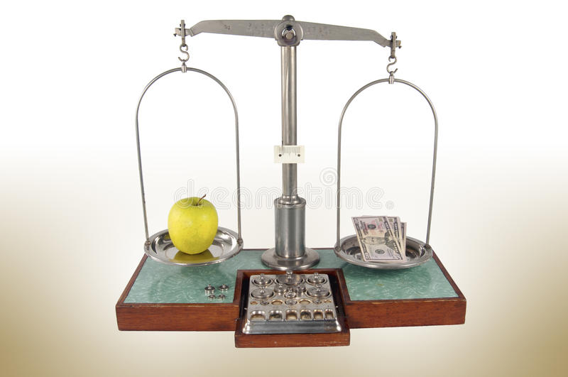 Old style pharmacy scale with money heavier than yellow apple. Traditional old style pharmacy scale with money heavier than yellow apple, small weights royalty free stock image